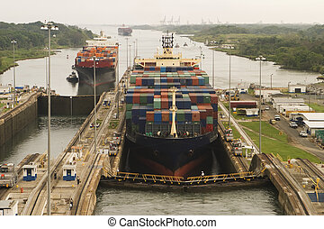 Panama Canal Commerce - Two freighters, assisted by...