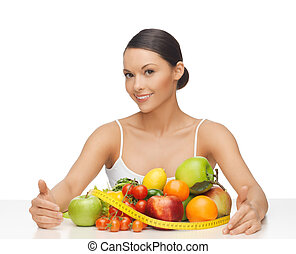 woman with measuring tape and lots of fruits