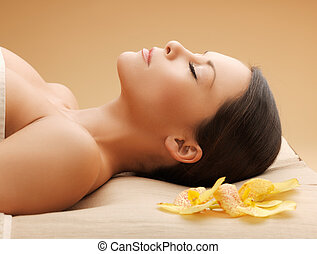 woman in spa salon lying on the massage desk