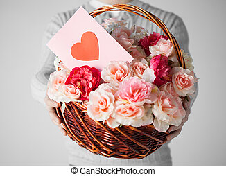 man holding basket full of flowers and postcard - close up...