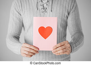 man holding postcard with heart shape - close up of man...