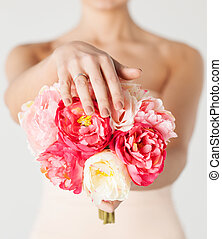 bride with bouquet of flowers and wedding ring - close up of...