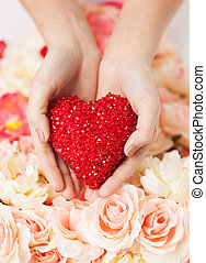 woman's hands holding heart - close up of woman's hands...