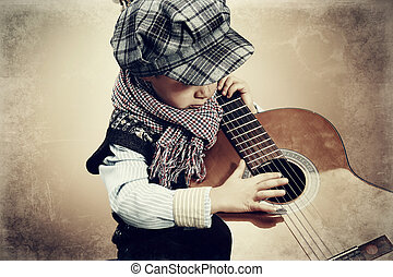 strings - Portrait of a romantic little boy with his guitar....