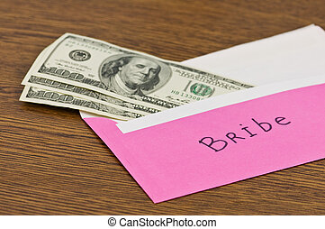 bribe - pink envelope with money on wood table