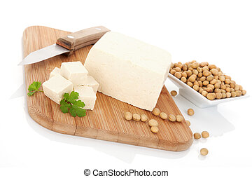 Soy background. - Tofu and soybeans on wooden kitchen board....