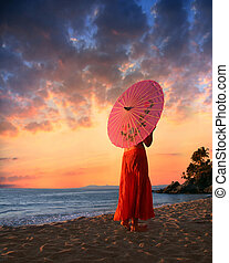 Girl with umbrella - A woman in orange skirt walking on a...