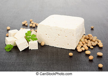 Delicious soya background. - Tofu and soybeans on black and...