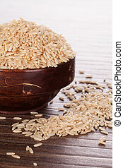 Brown rice background. - Brown rice in brown wooden round...
