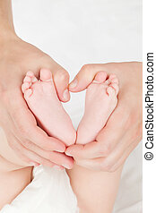 Mother hands holding baby feet.
