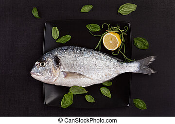 Sea bream on plate with herbs - One fresh gilt head bream on...