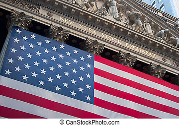 An American flag hangs on the front of the New York Stock...