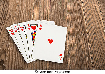 poker cards over an old wooden table. - Close up shot of...
