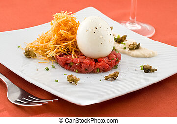 Gourmet dish with egg and raw meat.