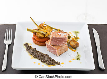 gourmet tuna dish with garnished vegetables and wine.