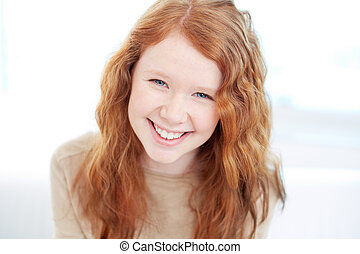 Smiley girl - Teenage girl with wavy ginger hair looking at...