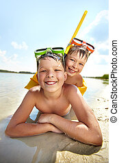 Siblings - Photo of happy siblings lying on sand on summer...