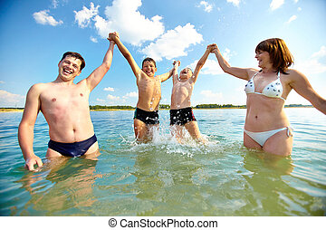 Having fun - Photo of happy family standing in water and...