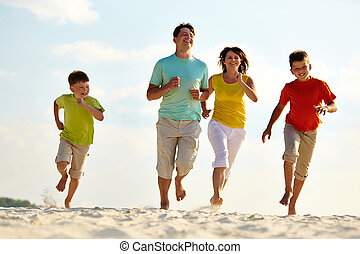 Activity - Photo of happy family running down the beach on...