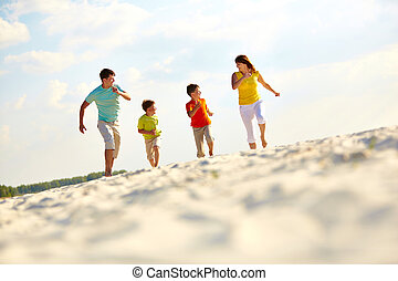 Happy time - Photo of happy family running down sandy beach...