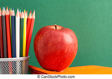 Apple and pencils - Close-up of big red apple on stack of...