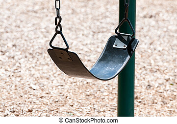 Up-close shot of swing at a playground.