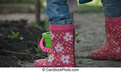 Child Playing in the Backyard - Child with a shovel and a...