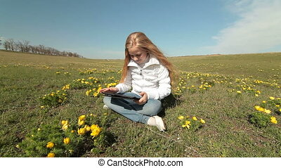 Child Using a Touch Screen Tablet - Little girl using a...