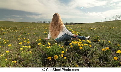 Child on a spring meadow - Little blonde girl sitting on a...