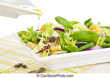Salad with olive oil. - Olive oil dropping on green fresh...