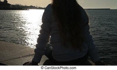 Little Girl On Embankment - Little girl sitting on the...