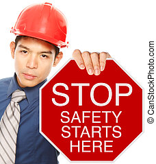 Safety Starts Here - A man wearing a hardhat holding a stop...