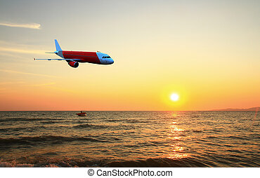 plane flying over sea at sunset