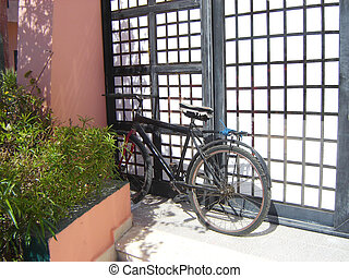 Black bicycle propped to wall