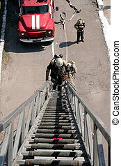 fireman on the stairs - fireman wearing a gas mask on the...