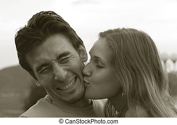 Portrait of a young couple. Girl kisses her boyfriend and he...