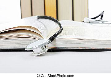 Stethoscope on open book against light background