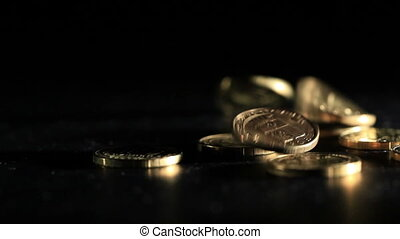 Gold coins falling over dark background. Real footage. Not cg.
