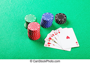 Royal flush of hearts and chips on green cloth