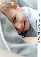 Happy smiling kid hiding in bedroom at home - Happy boy...