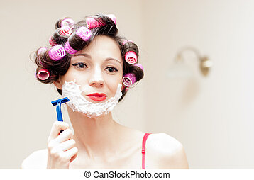 Beautiful funny girl shaving with foam & razor her face -...