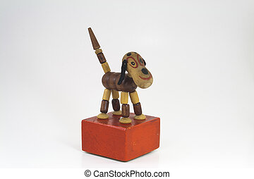 Toy Dog - Antique wooden toy dog on a red stand isolated on...