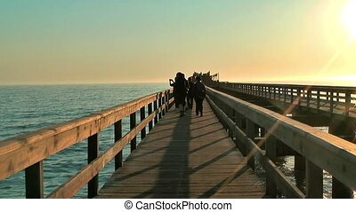 swakopmund jetty during sunset - Tourists walking on the...