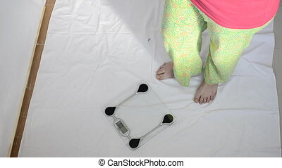 young pregnant woman measuring her weight