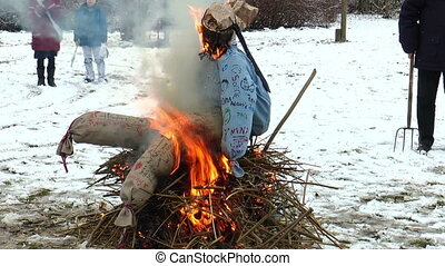 Burning a staw doll on funeral pyre - Old tradition driving...