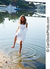 Young girl bride having fun on the splashing water in the river