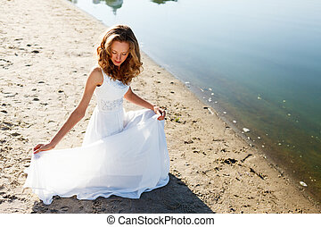 Elegant girl bridecrouched on a sandy river beach Sunny...
