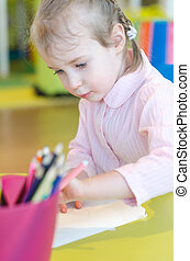 Little girl is drawing with pen in preschool