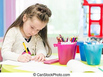Little girl is drawing with pen in preschool