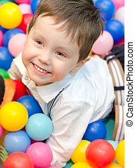 Happy little boy sitting in colourful balls